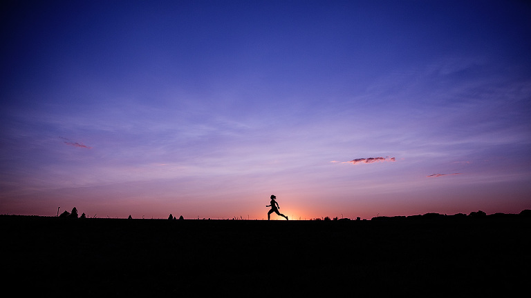 senior running in silhouette with a dramatic purple sky in rich